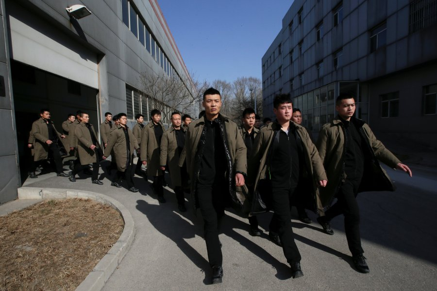 Trainees from Dewei Security walk for a daily training session at a training camp on the outskirts of Beijing