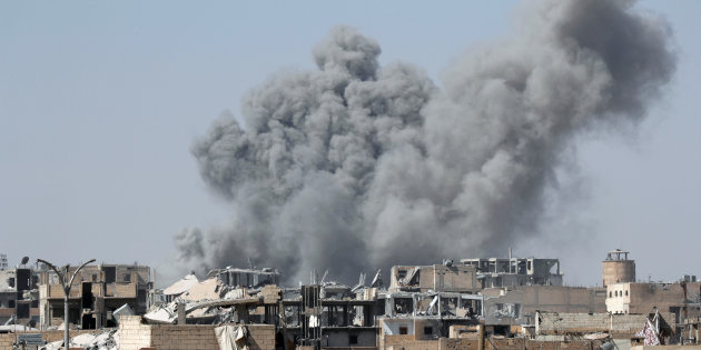 Smoke rises in the stadium as members of Syrian Democratic Forces battle with Islamic State militants in Raqqa