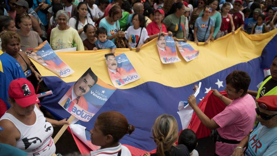 Supporters of Venezuela's President Nicolas Maduro hold placards with his image as they attend a campaign rally in Caracas