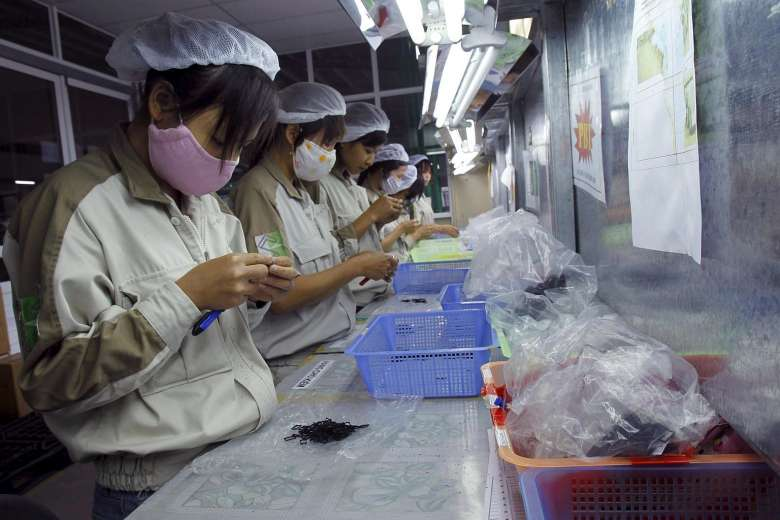 ASEAN Women working at a plastic factory, which makes plastic parts for electronic production, in Que Vo district, outside Hanoi. PHOTO REUTERS415