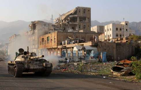 Yemeni fighters loyal to the country's exiled President Abedrabbo Mansour Hadi ride a tank past a destroyed building during clashes with Shiite Huthi rebels in the country's third-city of Taez on May 30, 2019. - Taez, in southern Yemen, is under siege by the Huthis but controlled by pro-government forces, who are supported by the military coalition led by Saudi Arabia and the United Arab Emirates. (Photo by Ahmad AL-BASHA / AFP)