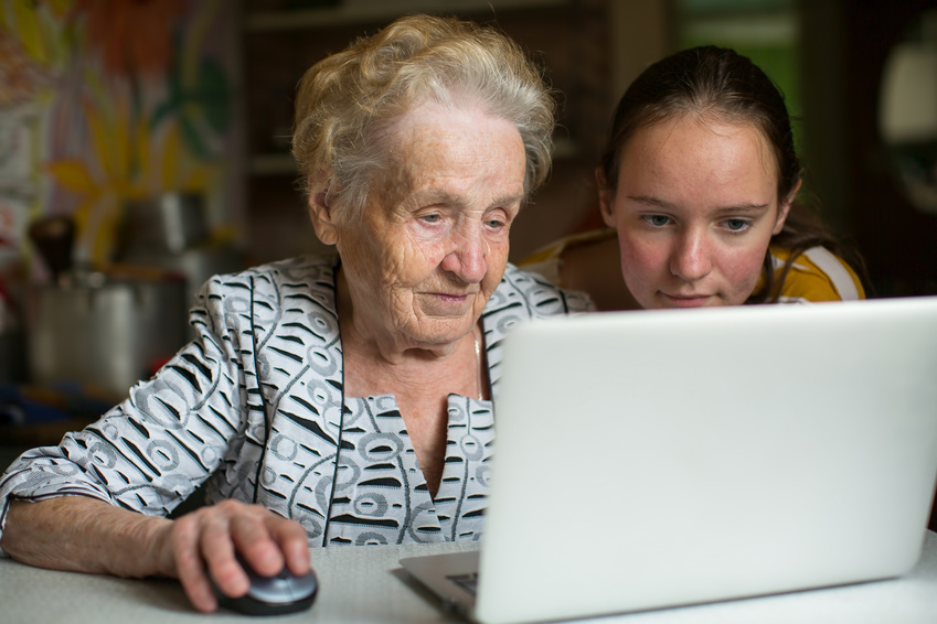 Elderly woman with her granddaughter working on laptop.
